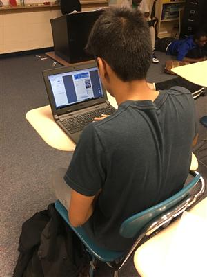 Student sitting in a desk working on a laptop